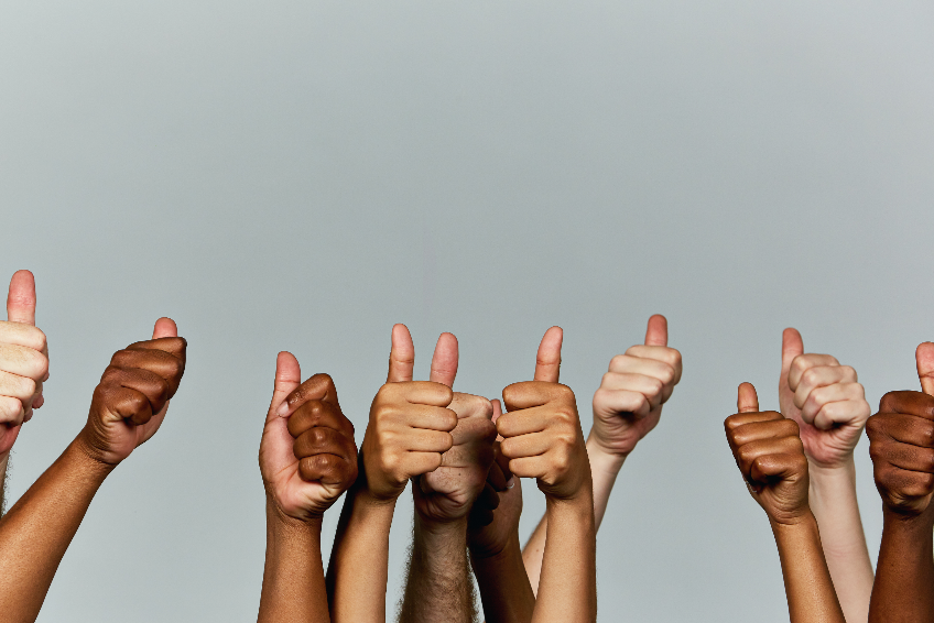 Many hands giving enthusiastic thumbs-up signals against gray background