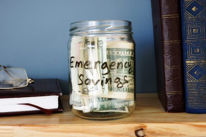 Jar with Emergency savings Cash Fund on the shelf.