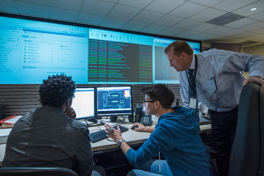 Colleagues working together in server control room