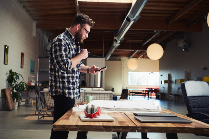 Architect standing at desk looking at mobile phone