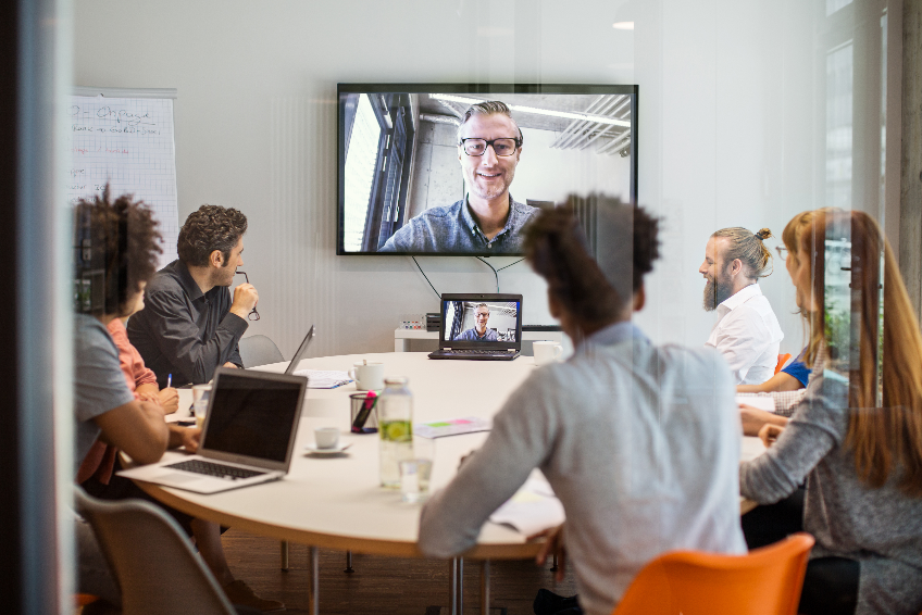 Business people having video conference meeting in board room