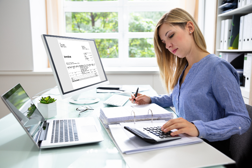 Young Businesswoman Calculating Bill In Office