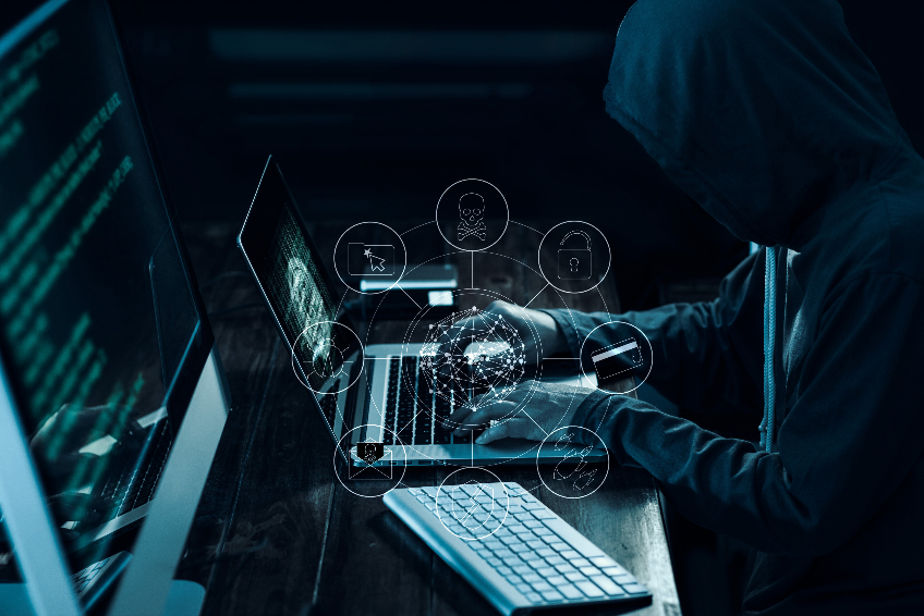 Computer hacker with icons working and stealing information on laptop in dark interface. Cyber crime concept