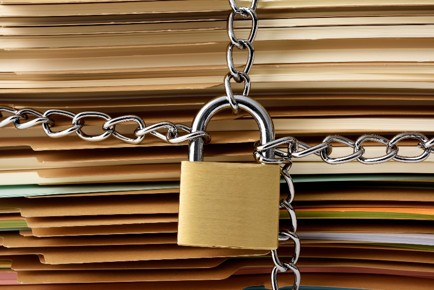 Close-up of stacked brown file folder with locked padlock