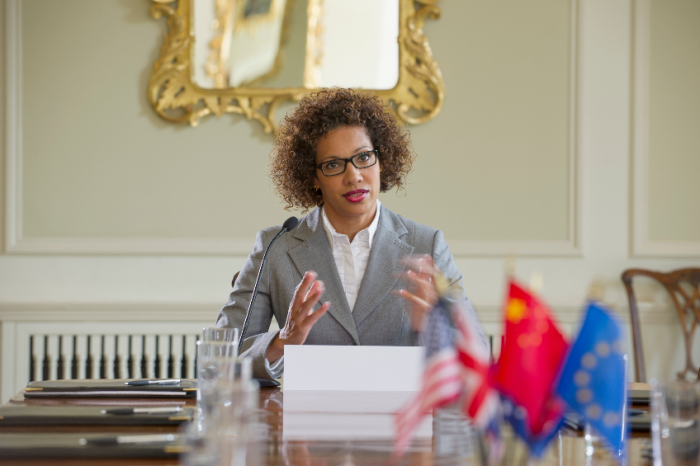 Mixed race businesswoman talking in microphone