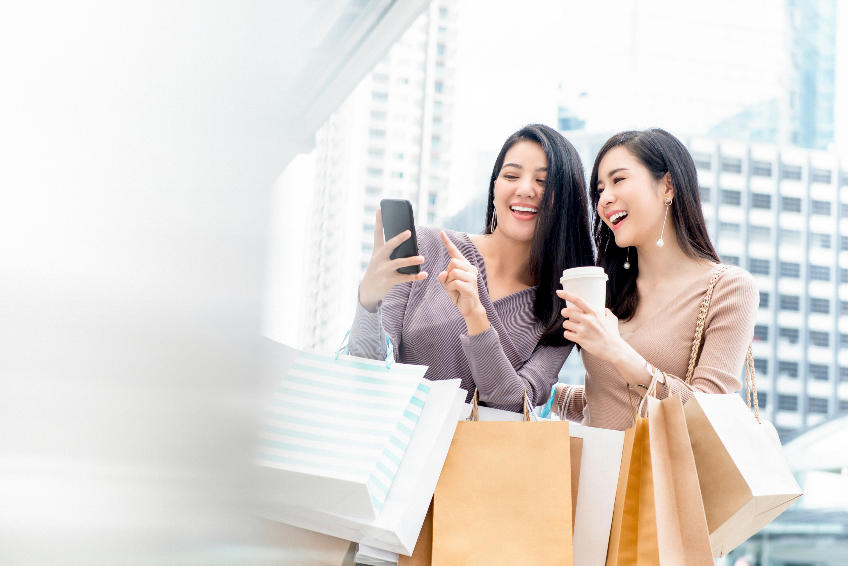 Beautiful Asian woman friends using smartphone while shopping in the city