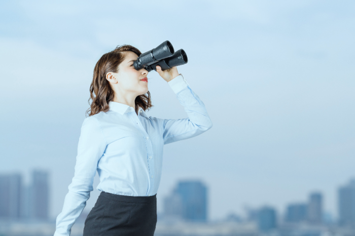 Young businesswoman using binoculars in front of the city.