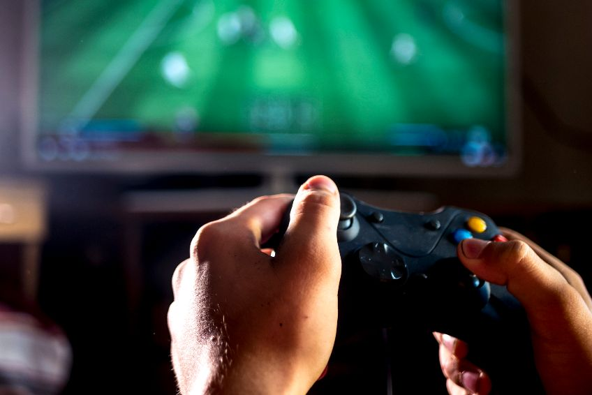 close up young man with joystick controller for console playing sport simulator video game on large screen