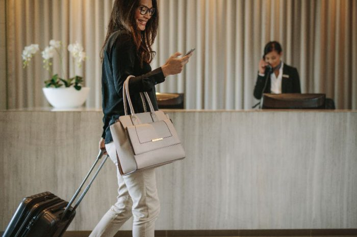 Business traveler in hotel hallway with phone