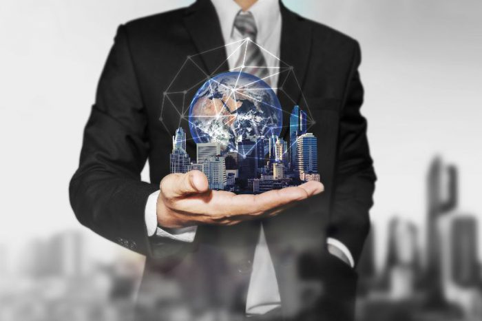 Businessman holding modern buildings with global network connection. Elements of this image are furnished by NASA