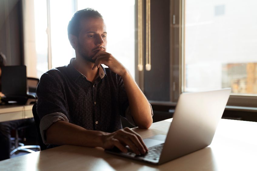 Casual Man Pensive on Computer