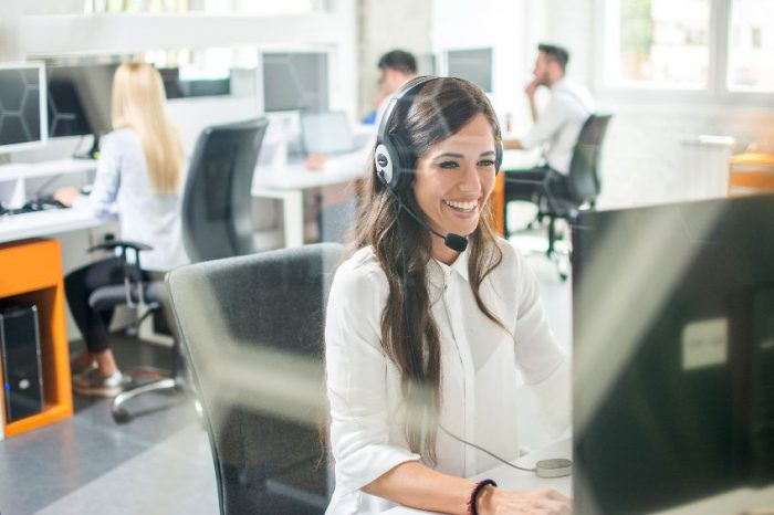 Beautiful smiling woman with headphones using computer while counseling at call center