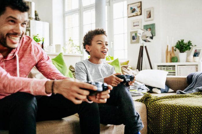 Young Boy Enjoying Himself Playing Video Games With Dad