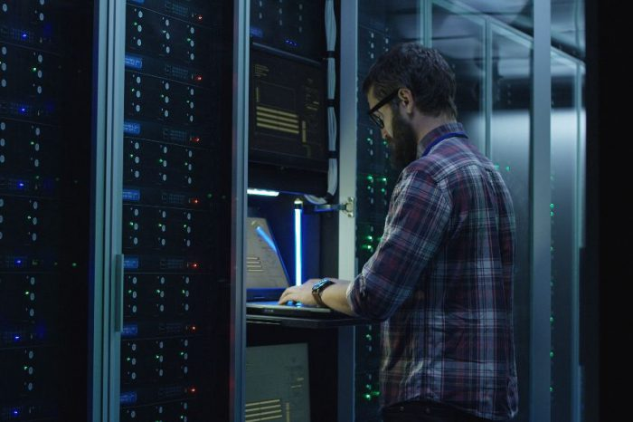 Bearded IT specialist setting servers in data center