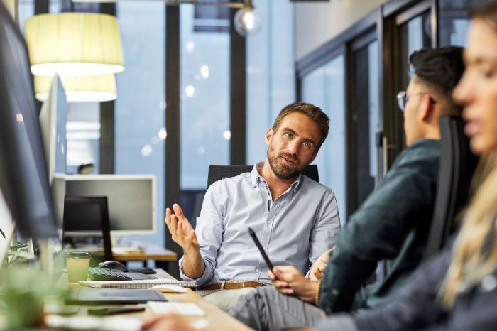 Male coworkers discussing during meeting in office