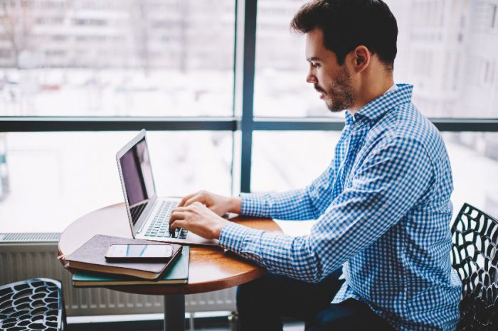 Concentrated male it professional working remotely typing text for new website using application on laptop computer, skilled man spending time on publicity area for e learning via online courses