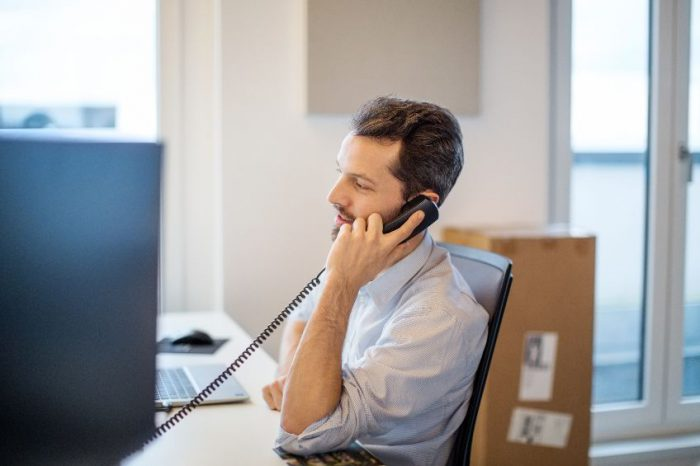 Businessman at his desk in office talking over telephone.