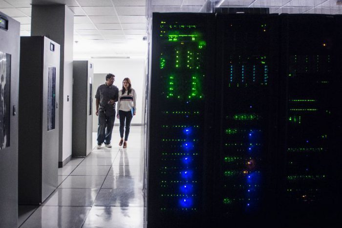 Colleagues walking in server room